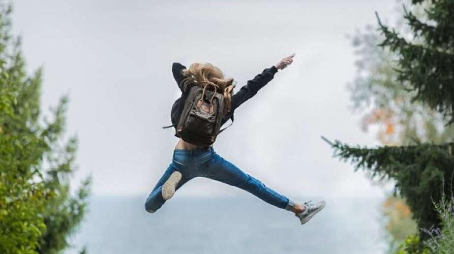 Donna salta davanti al mare