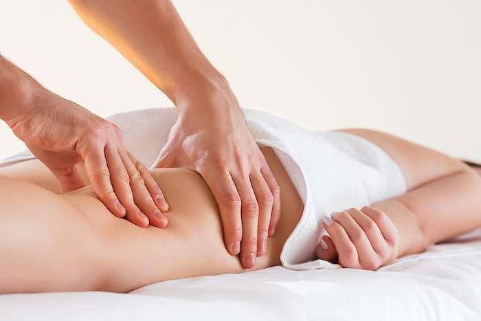 Dettaglio delle mani che massaggiano il muscolo del polpaccio umano Terapista che applica pressione sulla gamba femminile.